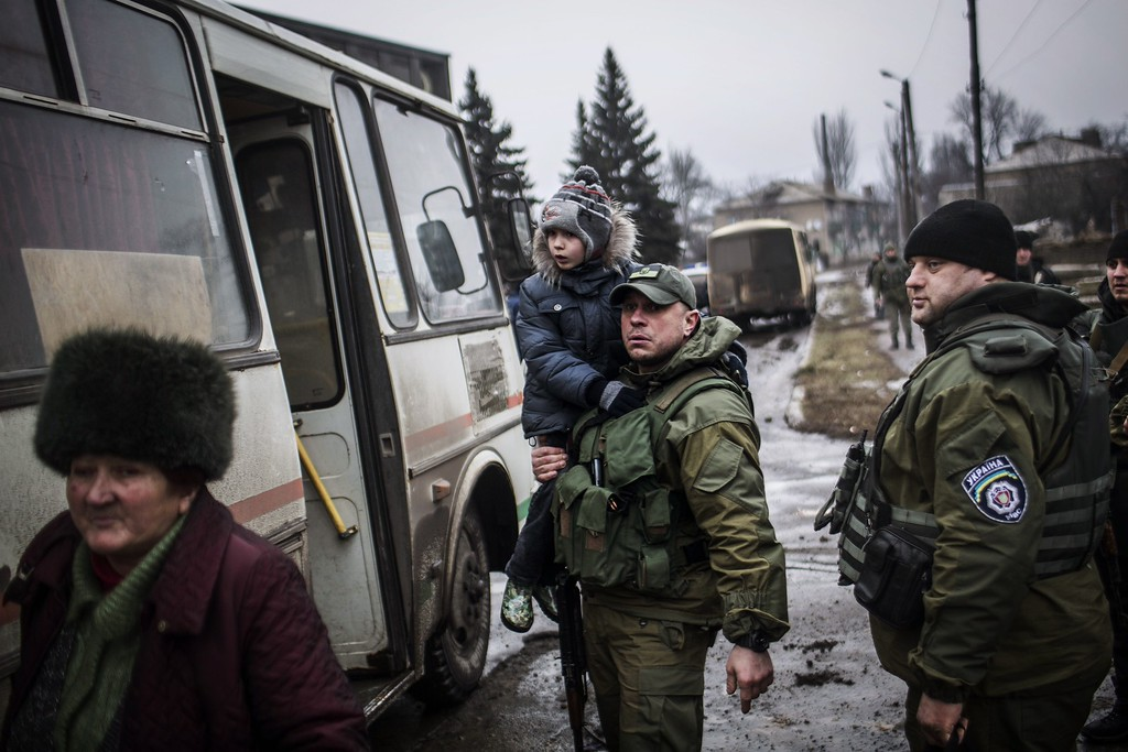 Description of . A Ukrainian army soldier holds a Ukrainian kid while evacuating citizens from Debaltseve, in the Donetsk region, on February 3, 2015. At least 19 civilians and five government troops were killed over the previous 24 hours as fierce clashes raged between pro-Russian separatists and Ukraine's outgunned forces in the east of the country, insurgent and government officials said. MANU BRABO/AFP/Getty Images