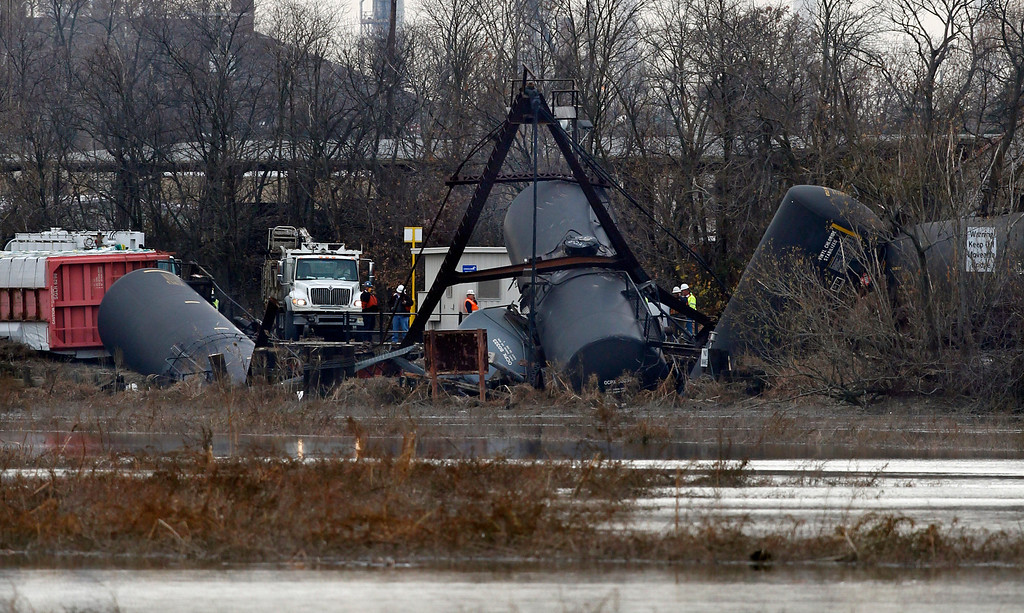 Description of . Derailed freight train tank cars are seen in Paulsboro, N.J., Friday, Nov. 30, 2012. People in three southern New Jersey towns were told Friday to stay inside after a freight train derailed and several tanker cars carrying hazardous materials toppled from a bridge and into a creek. At least one tanker car may contain vinyl chloride, Gloucester County Emergency Management director J. Thomas Butts told WPVI-TV. (AP Photo/Mel Evans)