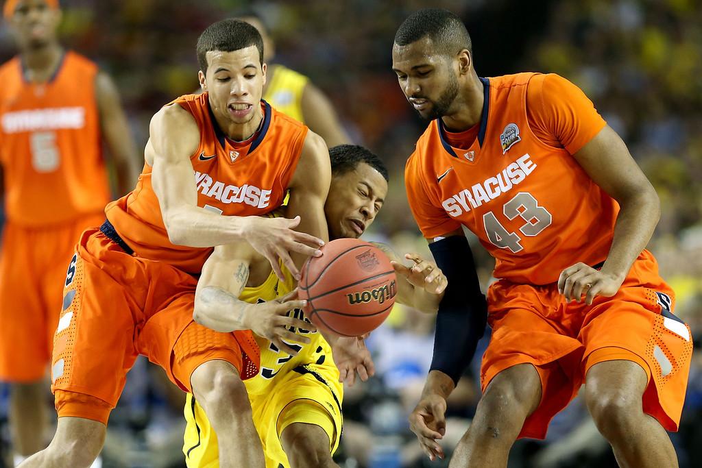 Description of . ATLANTA, GA - APRIL 06:  Trey Burke #3 of the Michigan Wolverines attempts to control the ball in the first half against Michael Carter-Williams #1 and James Southerland #43 of the Syracuse Orange during the 2013 NCAA Men's Final Four Semifinal at the Georgia Dome on April 6, 2013 in Atlanta, Georgia.  (Photo by Streeter Lecka/Getty Images)