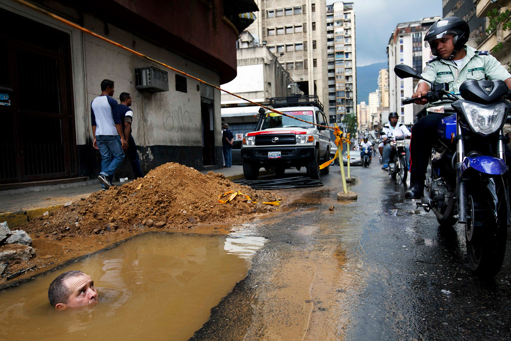 . In this Sept. 26, 2012 file photo, a worker is seen partially submerged under water as he tries to repair a broken pipe in Caracas, Venezuela. (AP Photo/Rodrigo Abd, File)