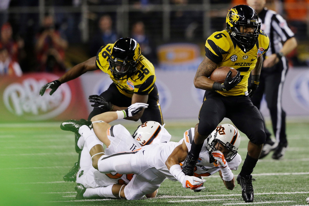 Description of . Missouri running back Marcus Murphy (6) breaks a tackle-attempt by Oklahoma State cornerback Miketavius Jones (24) during the first half of the Cotton Bowl NCAA college football game on Friday, Jan. 3, 2014, in Arlington, Texas. (AP Photo/Tim Sharp)