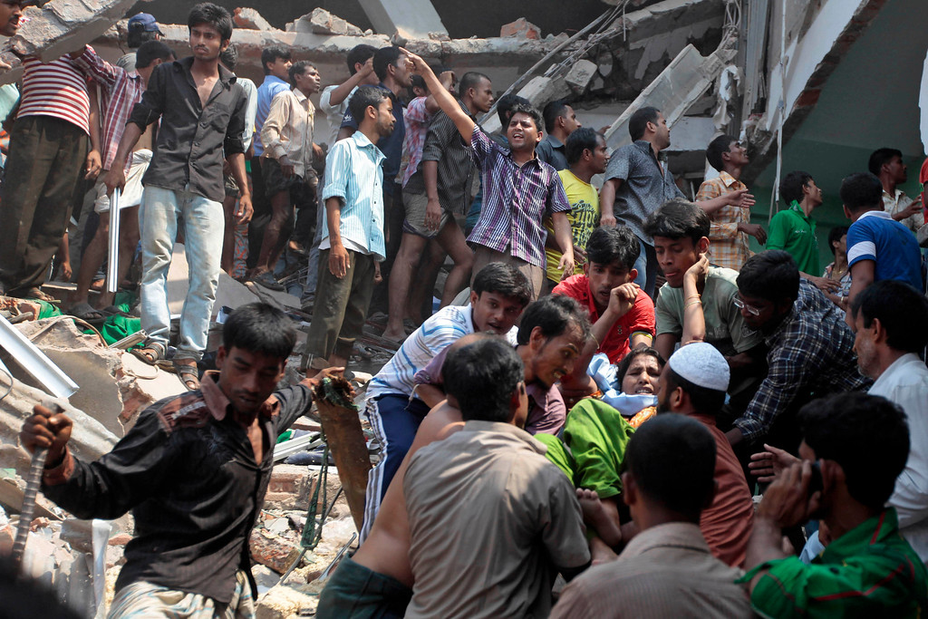 Description of . A woman, facing the camera on right, who was trapped in a collapsed eight-story building housing several garment factories, is rescued in Savar, near Dhaka, Bangladesh, Wednesday, April 24, 2013.(AP Photo/ A.M. Ahad)