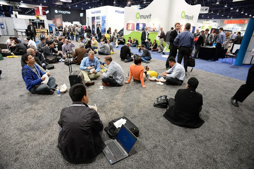 Description of . Attendees sit on the floor of the North Hall of the Las Vegas Convention Center as they eat lunch during the 2014 International CES in Las Vegas, Nevada, January 8, 2014.   AFP PHOTO / ROBYN BECK/AFP/Getty Images