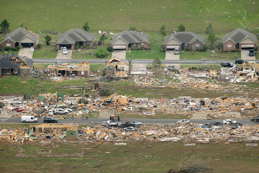 Description of . A row of lightly damages houses, top, face destroyed homes in a Vilonia, Ark., neighborhood Monday, April 28, 2014 after a tornado struck the town late Sunday, killing at least 16 people.   (AP Photo/Danny Johnston)