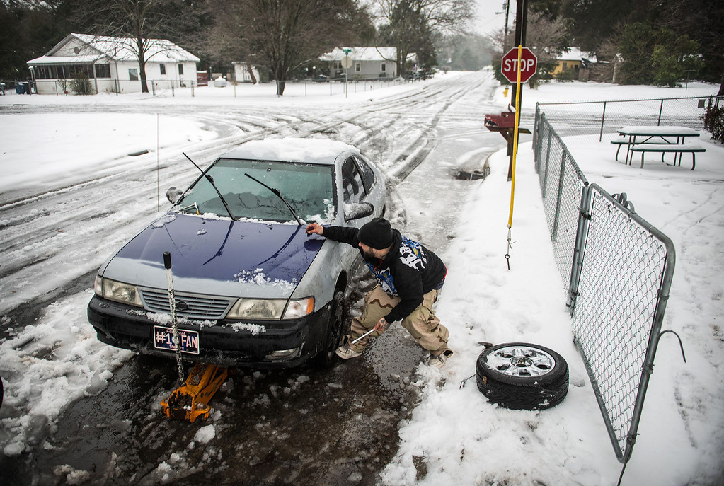 Description of . Phil Giordano changes the bald tires on his car along snowy Center St. in the Massey Hill community in Fayetteville, N.C., Thursday morning, Feb. 13, 2014.  A major winter storm Wednesday brought a mixture of snow, sleet and freezing rain to North Carolina. (AP Photo/The Fayetteville Observer,  James Robinson)