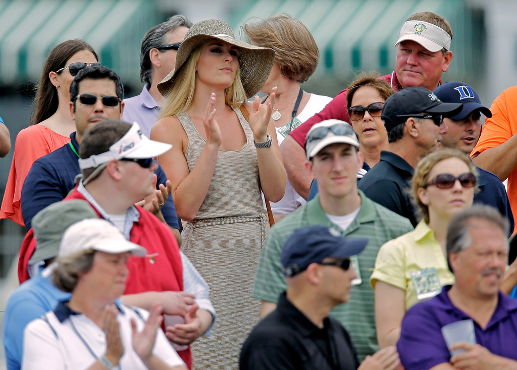 Description of . Skier Lindsey Vonn applauds as she watches Tiger Woods  during the first round of the Masters golf tournament Thursday, April 11, 2013, in Augusta, Ga. (AP Photo/Matt Slocum)