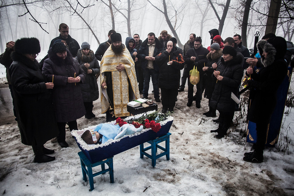 Description of . Mourners gather around a coffin bearing Artiam, 4, who was killed in a Ukrainian army artillery strike, during his funeral in Kuivisevsky district on the outskirts of Donetsk, eastern Ukraine, Tuesday, Jan. 20, 2015. At least three civilians were killed in shelling Tuesday in eastern Ukraine as fighting continued between government and rebel forces in the separatist-held city of Donetsk. (AP Photo/Manu Brabo)