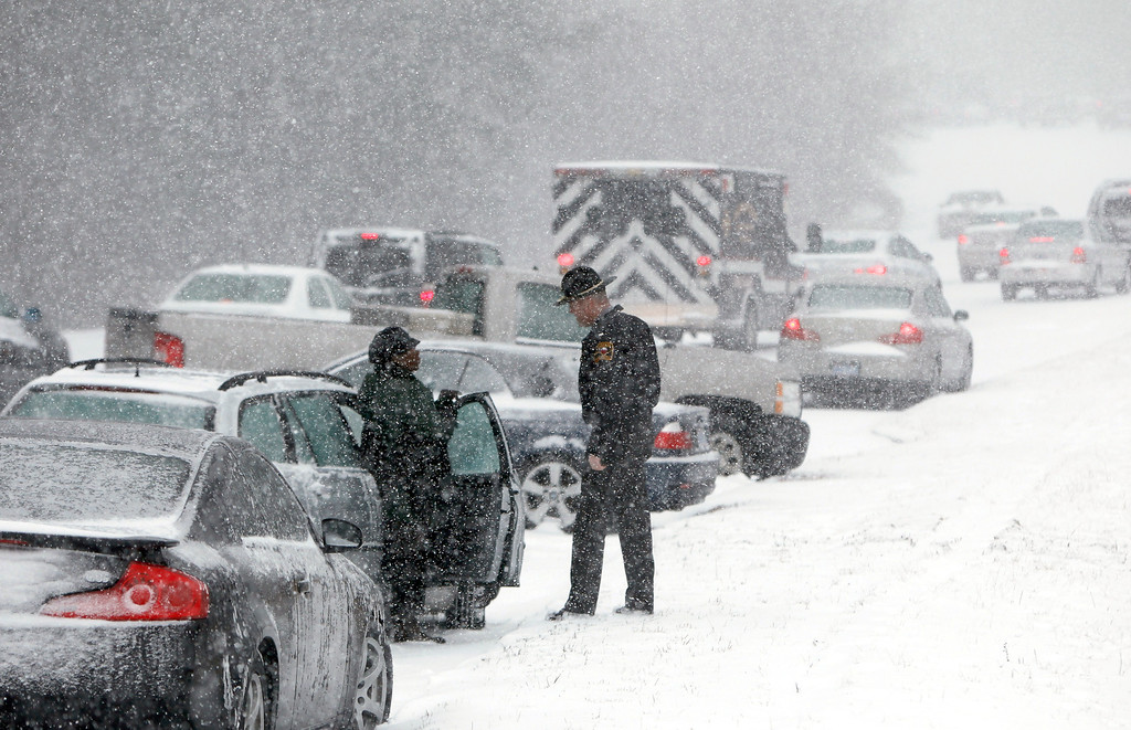 Description of . A Highway Patrol officer checks on the well being of a stranded motorist on Hammond Road during a winter storm Wednesday Feb. 12, 2014, in Raleigh, N.C. (AP Photo/The News & Observer, Travis Long)