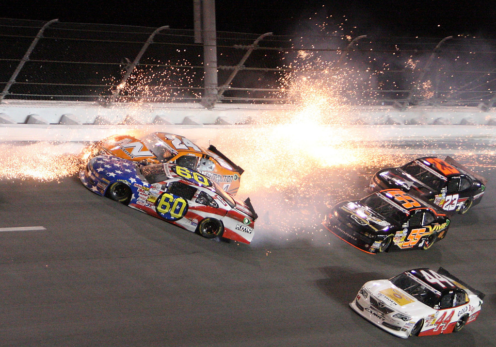 Description of . Travis Pastrana (60) crashes into Jason White (24) in turn 4 of the NASCAR Nationwide auto race at Daytona International Speedway, Friday, July 5, 2013, in Daytona Beach, Fla. (AP Photo/Darryl Graham)