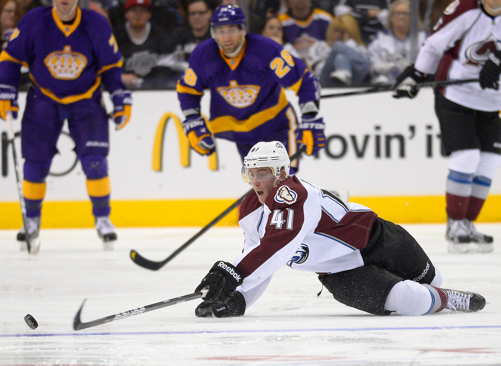 Description of . Colorado Avalanche defenseman Tyson Barrie, right, dives for  the puck as Los Angeles Kings center Jarret Stoll looks on during the second period of their NHL hockey game, Saturday, Feb. 23, 2013, in Los Angeles. (AP Photo/Mark J. Terrill)
