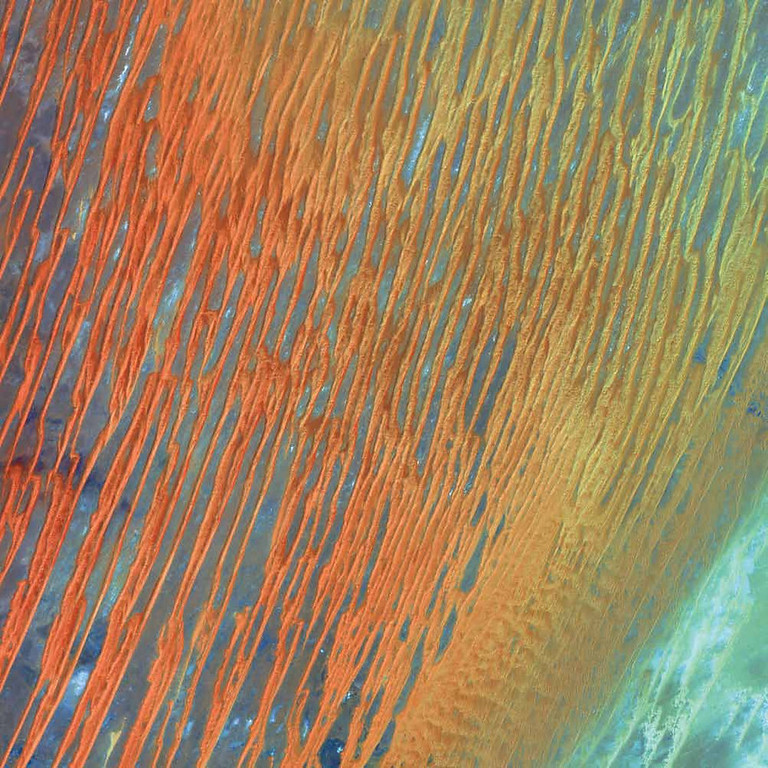 Description of . Erg Chech, Algeria In this Landsat 7 image from 2003, the amber and caramel lattices seen are large, linear sand dunes in the Erg Chech dune sea located in the Sahara region of western Algeria. An erg, meaning dune field in Arabic, is a wide, flat area of desert covered with windblown sand and little vegetation cover. The dunes are formed when large amounts of transported sand are halted by topographic barriers. The largest dunes can take up to a million years to build. Ergs are also found on other celestial bodies such as Venus, Mars, and Saturn�s moon Titan.   NASA