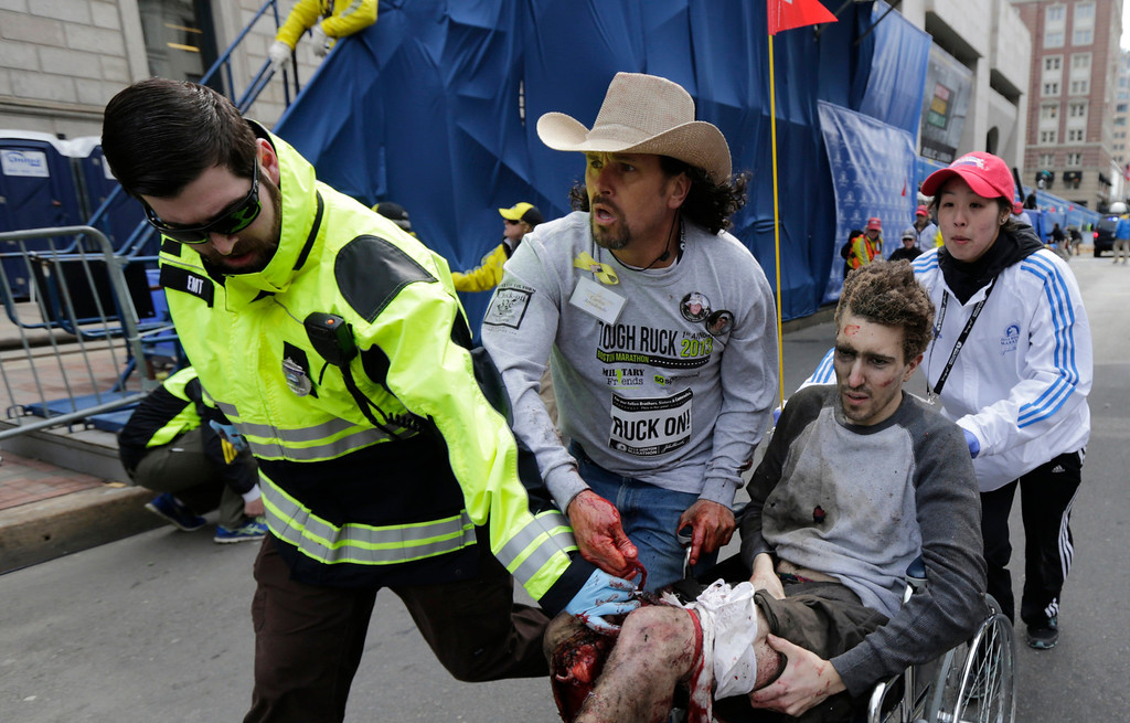 Description of . An emergency responder and volunteers, including Carlos Arredondo in the cowboy hat, push Jeff Bauman in a wheel chair after he was injured in an explosion near the finish line of the Boston Marathon Monday, April 15, 2013 in Boston.  (AP Photo/Charles Krupa)