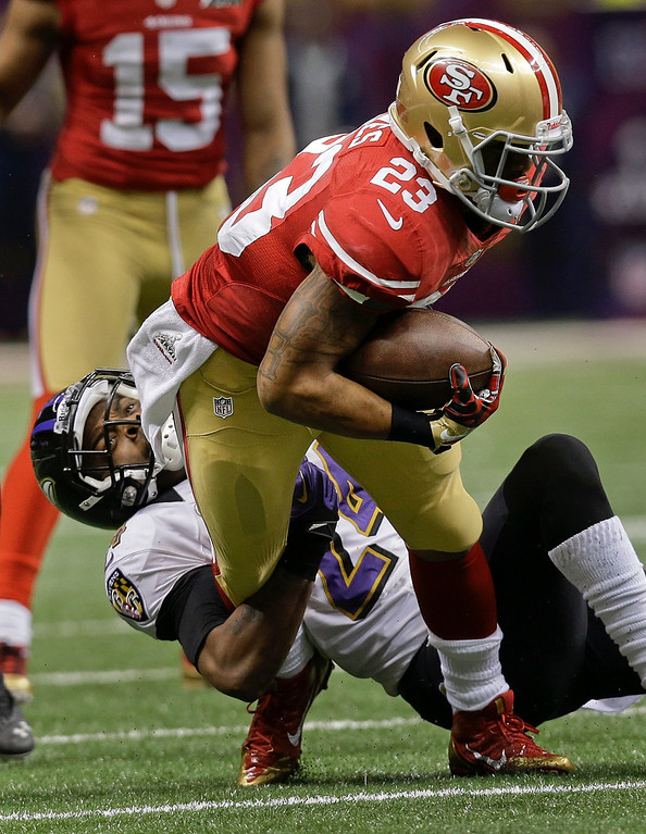 Description of . Baltimore Ravens cornerback Corey Graham (24) pulls down San Francisco 49ers running back LaMichael James (23) in the second quarter of the NFL Super Bowl XLVII football game, Sunday, Feb. 3, 2013, in New Orleans. (AP Photo/Dave Martin)