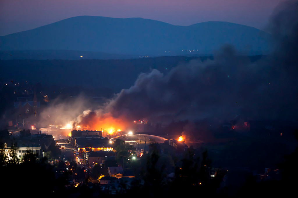 Description of . Firefighters douse blazes after a freight train loaded with oil derailed in Lac-Megantic in Canada's Quebec province on July 6, 2013, sparking explosions that engulfed about 30 buildings in fire.  At least 40 people are missing after a driverless oil tanker train derailed and exploded in the small Canadian town of Lac-Megantic, destroying dozens of buildings, a firefighter back from the scene told AFP.    Franois Laplante-Delagrave/AFP/Getty Images