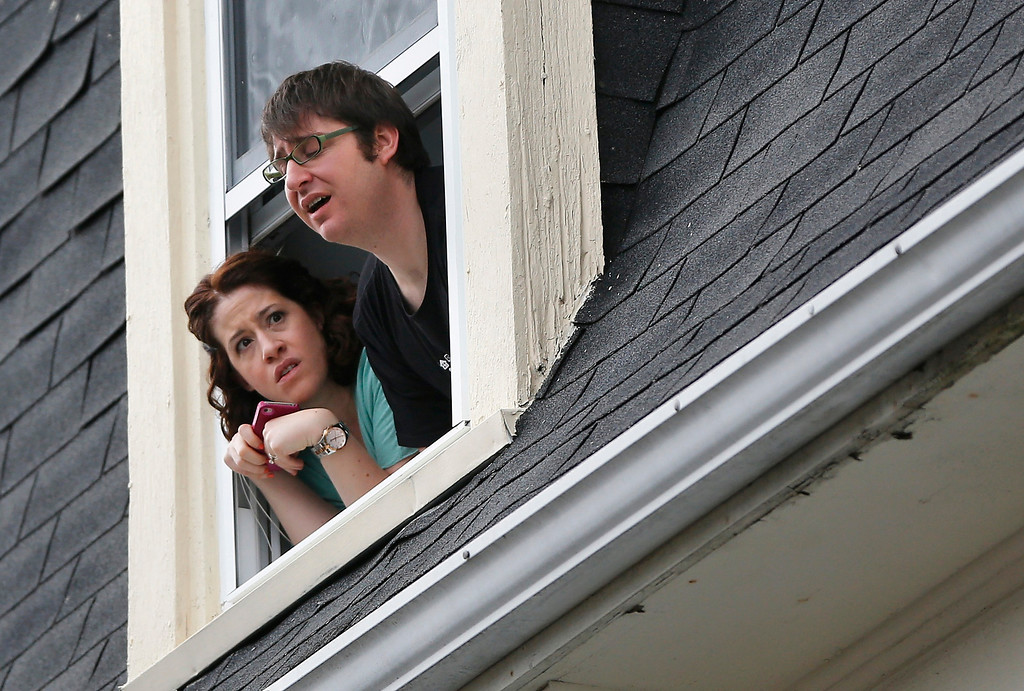Description of . People look through a window after a flash-bang was set off at 410 Norfolk Street in Cambridge, Massachusetts April 19, 2013.    REUTERS/Shannon Stapleton