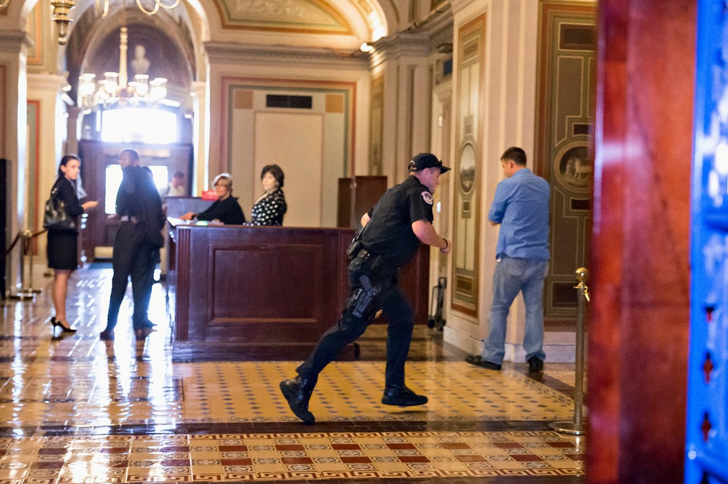 Description of . A Capitol Police officer runs through the first floor of the Senate on Capitol Hill in Washington, Thursday, Oct. 3,2013, during the lockdown order following a shooting on Constitution Avenue on Capitol Hll and near the Supreme Court. A police officer was reported injured after gunshots at the U.S. Capitol, police said Thursday. They locked down the entire complex, at least temporarily derailing debate over how to end a government shutdown.   (AP Photo/J. Scott Applewhite)