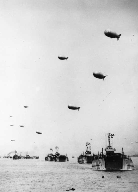 Description of . A long line of LST or Landing Ship-Tanks, each towing a protective barrage balloon, are seen heading away from the English coast carrying supplies to the French beachhead June 6, 1944.  (Photo by Keystone/Getty Images)
