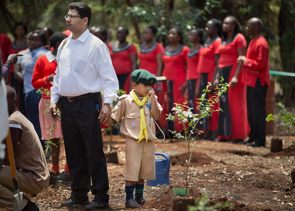 Description of . Khalil Rashid, 6, wears a scouts uniform as he holds the hand of his father and waits to plant a tree in memory of his schoolmate Jennah Bawa, 8, from Britain, who was shot along with her mother Zahira, at a memorial service and tree-planting marking the one-month anniversary of the the Sept. 21 Westgate Mall terrorist attack, in Karura Forest in Nairobi, Kenya Monday, Oct. 21, 2013.  (AP Photo/Ben Curtis)