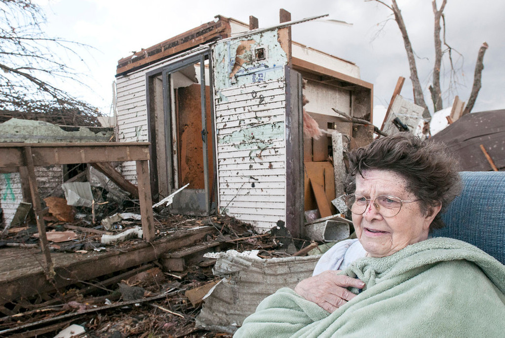 Description of . Pat Whitaker, 82, sits under a blanket in her nightgown outside her home waiting for help to come in Gifford, Ill. on Sunday, Nov. 17, 2013. Intense thunderstorms and tornadoes swept across the Midwest, causing extensive damage in several central Illinois communities while sending people to their basements for shelter. (AP Photo/The News-Gazette, Robin Scholz)