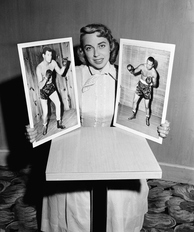 Description of . Dr. Joyce Brothers, child psychologist who hit the $64,000 jackpot in quiz on boxing knowledge is shown with photos of boxers James J. Parker, left, and opponent Archie Moore, July 22, 1956. (AP Photo)