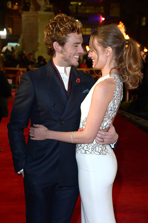 Description of . English actors Sam Claflin and Laura Haddock pose for photographers as they arrive on the red carpet for the World Premiere of 'The Hunger Games: Catching Fire', in London, Monday Nov. 11, 2013. 'Catching Fire' is the second installment in 'The Hunger Games' trilogy. (Photo by Jon Furniss/Invision/AP)