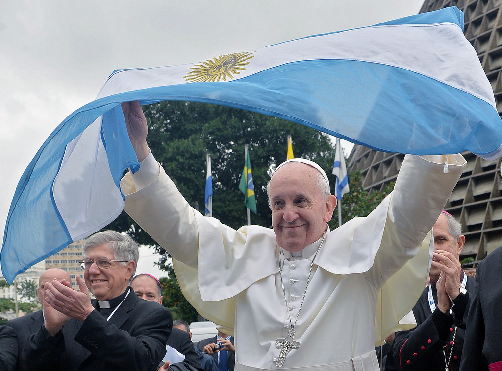 Description of . Pope Francis flutters an Argentine flag outside the Metropolitan cathedral in Rio de Janeiro, Brazil on July 25, 2013. The first Latin American and Jesuit pontiff arrived in Brazil mainly for the huge five-day Catholic gathering World Youth Day. LUCA ZENNARO/AFP/Getty Images