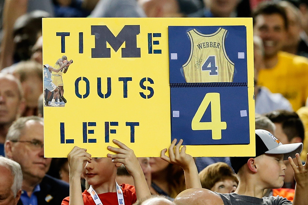 Description of . ATLANTA, GA - APRIL 06:  A fan holds up a sign which reads as a TImeout counter in reference to former Michigan Wolverines player Chris Webber as Michigan plays against the Syracuse Orange during the 2013 NCAA Men's Final Four Semifinal at the Georgia Dome on April 6, 2013 in Atlanta, Georgia.  (Photo by Kevin C. Cox/Getty Images)