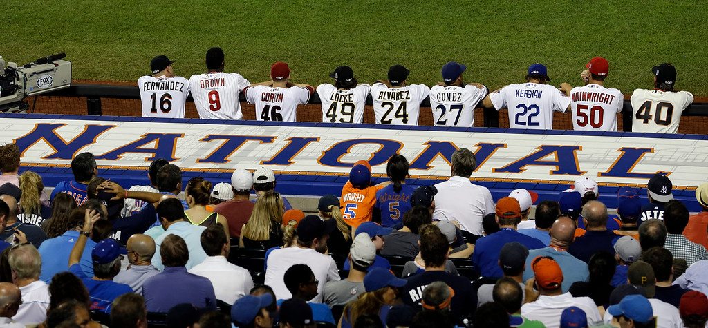 Description of . National League players watch from the dugout  during the sixth inning of the MLB All-Star baseball game, on Tuesday, July 16, 2013, in New York. (AP Photo/Julio Cortez)