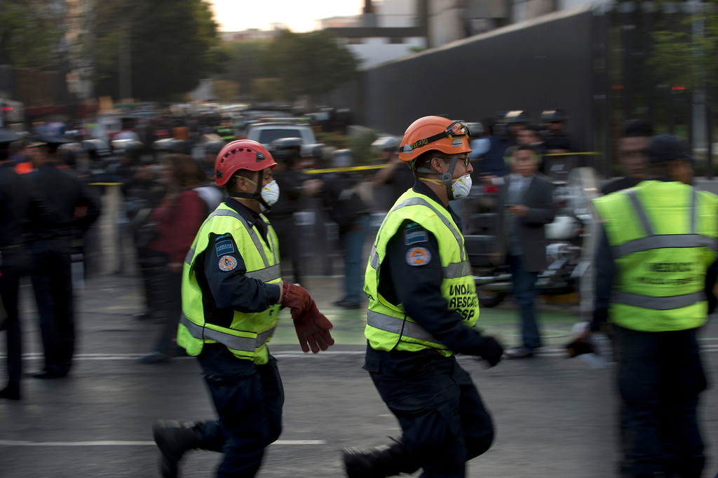 Description of . Rescue workers head for the skyscraper that houses the headquarters of state-owned Mexican oil giant Pemex in Mexico City on January 31, 2013, following a blast inside the building.     YURI CORTEZ/AFP/Getty Images