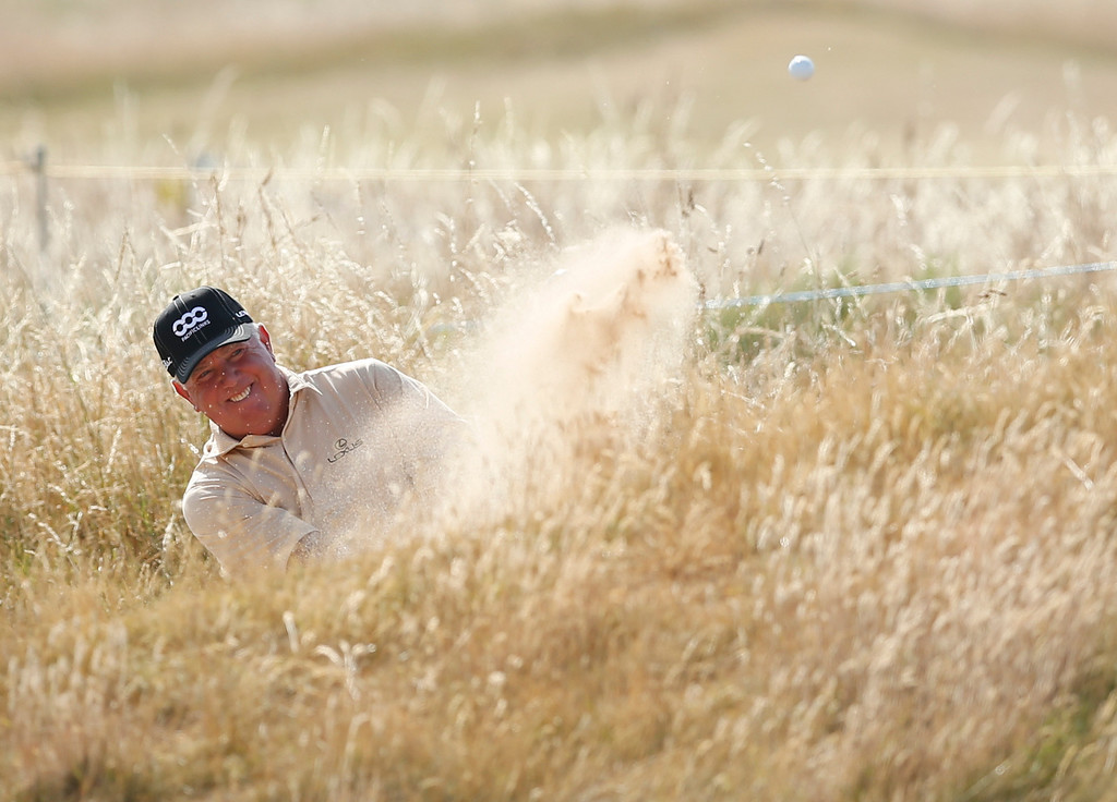 Description of . Mark O'Meara of the United States plays out of a bunker on the 16th hole during the third round of the British Open Golf Championship at Muirfield, Scotland, Saturday July 20, 2013. (AP Photo/Matt Dunham)