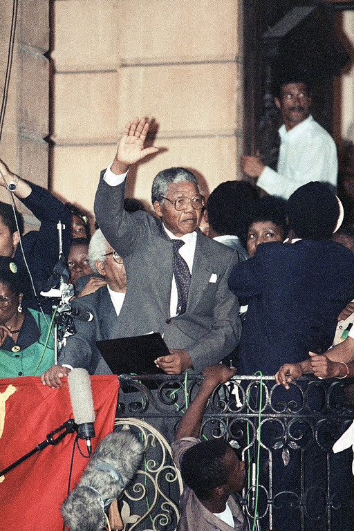 Description of . ANC leader Nelson Mandela waves too thousands of his supporters on Sunday, February 11, 1990 in Cape Town during his address in freedom after spending 27 years in jail. (AP Photo)