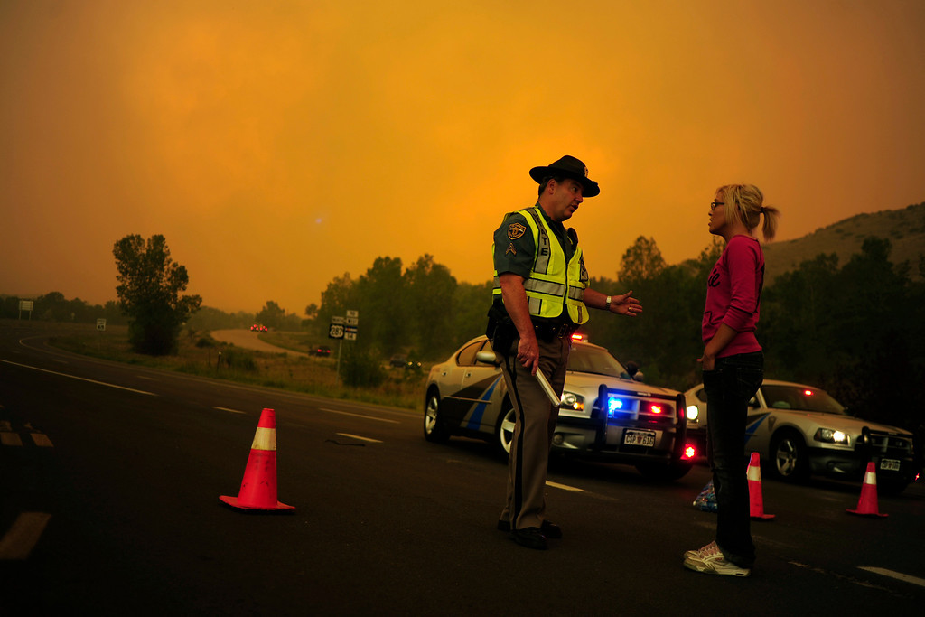 Description of . Trooper Kenner speaks with Brittany Harrington at a road closure on Highway 287 as the High Park fire burns west of Fort Collins and Loveland on Sunday, June 10, 2012. Harrington's home was blocked off due to the road closure, but she was able to walk with her boyfriend to their house. The rapidly growing High Park fire is now burning an estimated 2,000 to 3,000 acres west of Fort Collins and Loveland, according to the Larimer County Sheriff's Office. AAron Ontiveroz, The Denver Post
