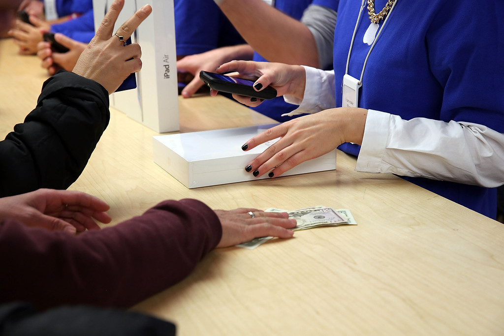 Description of . People buy the new Apple iPad Air at the Apple Store on November 1, 2013 in New York City.  (Photo by Spencer Platt/Getty Images)
