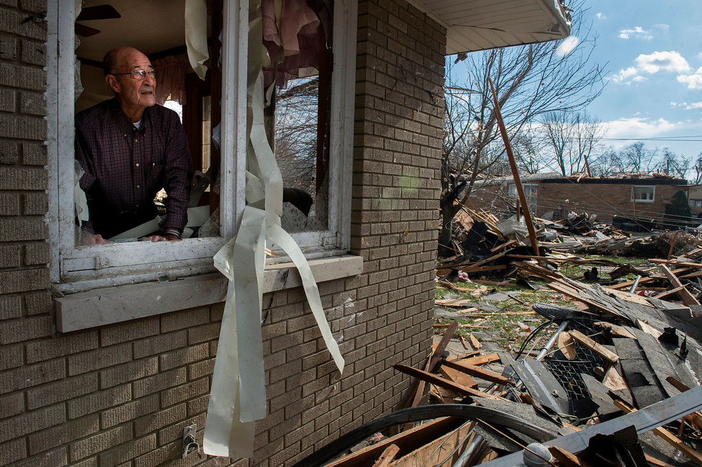 Description of . Chuck Phillips looks out at the destruction that tore off part of his roof and left houses around him destroyed after a tornado left a path of devastation through the north end of Pekin, Il.,Sunday, Nov. 17, 2013. Intense thunderstorms and tornadoes swept across the Midwest on Sunday, causing extensive damage in several central Illinois communities while sending people to their basements for shelter. (AP Photo/Journal Star, Fred Zwicky)