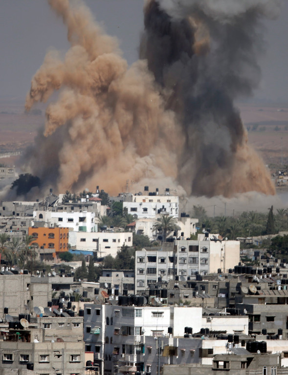 Description of . Smoke and sand from an explosion rise after an Israeli strike in Gaza City, northern Gaza Strip, Thursday, July 31, 2014.(AP Photo/Majed Hamdan)