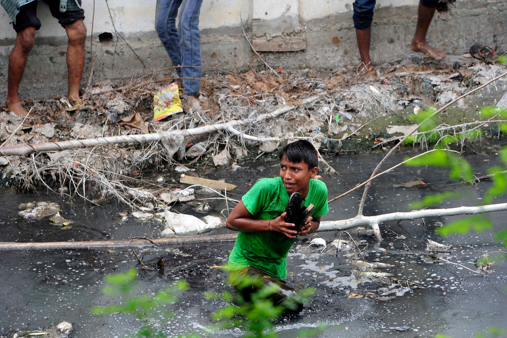 Description of . A protester takes shelter in a drain after police charge with batons during a demonstration in Savar, outside Dhaka April 30, 2013. The protesters were demonstrating to demand capital punishment for those responsible for the collapse of the Rana Plaza building in Savar. REUTERS/Khurshed Rinku