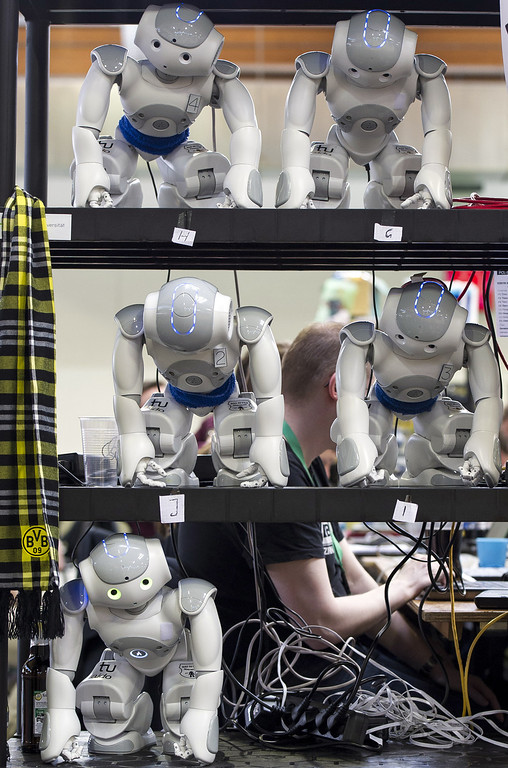 Description of . MAGDEBURG, GERMANY - APRIL 26:  Robots stand at a shelf near the play field at the 2013 RoboCup German Open tournament on April 26, 2013 in Magdeburg, Germany. The robots, which are a model called Nao, manufactured by Aldebaran Robotics, perform autonomously and communicate with one another via WLAN. The three-day tournament is hosting 43 international teams and 158 German junior teams that compete in a variety of disciplines, including soccer, rescue and dance.  (Photo by Jens Schlueter/Getty Images)