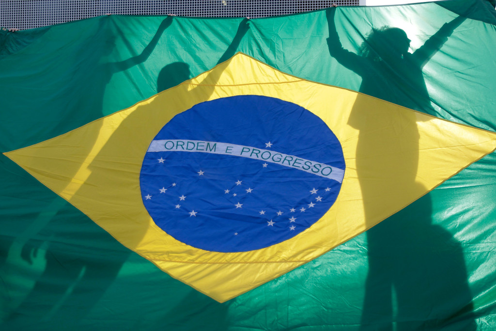 Description of . Demonstrators hold a Brazilian flag during a protest in front of the Brazilian National Congress in Brasilia, Brazil, Monday, June 17, 2013. Protesters massed in at least seven Brazilian cities Monday for another round of demonstrations voicing disgruntlement about life in the country, raising questions about security during big events like the current Confederations Cup and a papal visit next month. (AP Photo/Eraldo Peres)