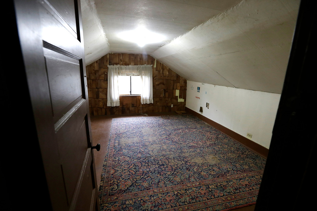 Description of . In this photo taken Monday, Sept. 23, 2013, an attic bedroom used by Kurt Cobain, the late frontman of Nirvana, is said by realtors to still include the original rug from when he lived in his childhood home in Aberdeen, Wash. (AP Photo/Elaine Thompson)