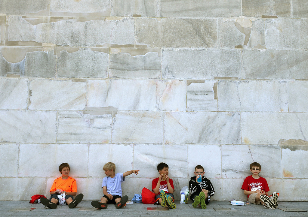 . Recent repairs are visible as 5th graders (L-R), Jacob Smith-Osborn, Dom Balzano, Jiashu Chen, James Downs ans Alex Musshorn have lunch in the shade of the newly re-opened Washington Monument May 12, 2014 in Washington, DC.   (Photo by Mark Wilson/Getty Images)