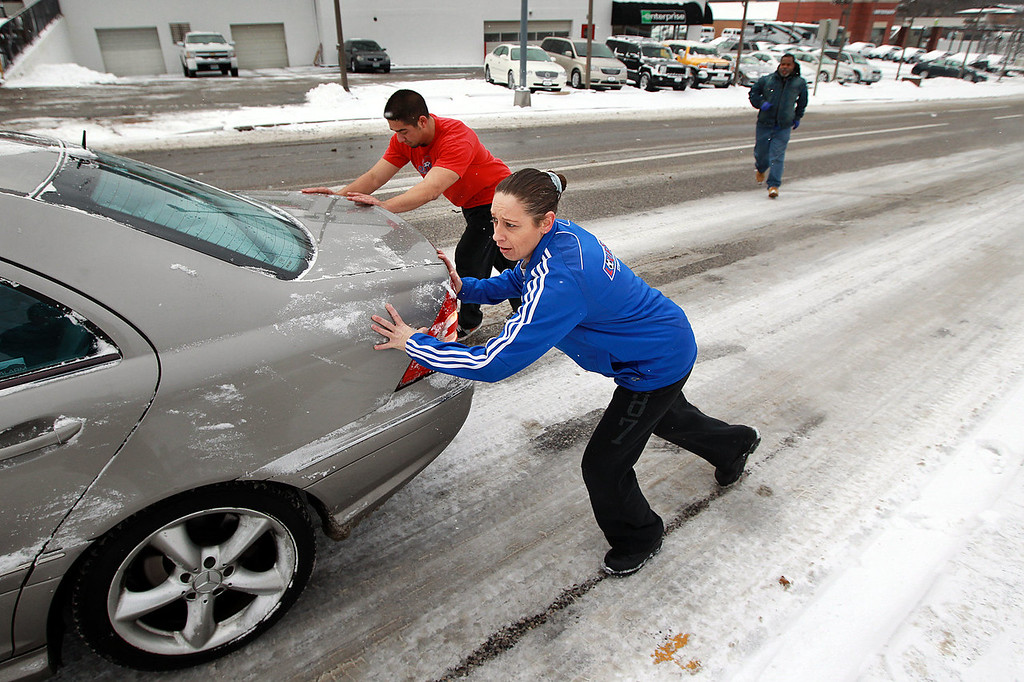 Description of . Elaine Gronewald, foreground, and Cory Bachesta, workers at the nearby Lou Fusz shop, help a stranded motorist on a slippery and hilly portion of a road Thursday, Jan. 2, 2014, in Kirkwood, Mo., a St. Loius suburb. Snow began falling Wednesday and continued into Thursday morning, coating the ground with 2- to 5-inches. (AP Photo/St. Louis Post-Dispatch, Huy Mach)