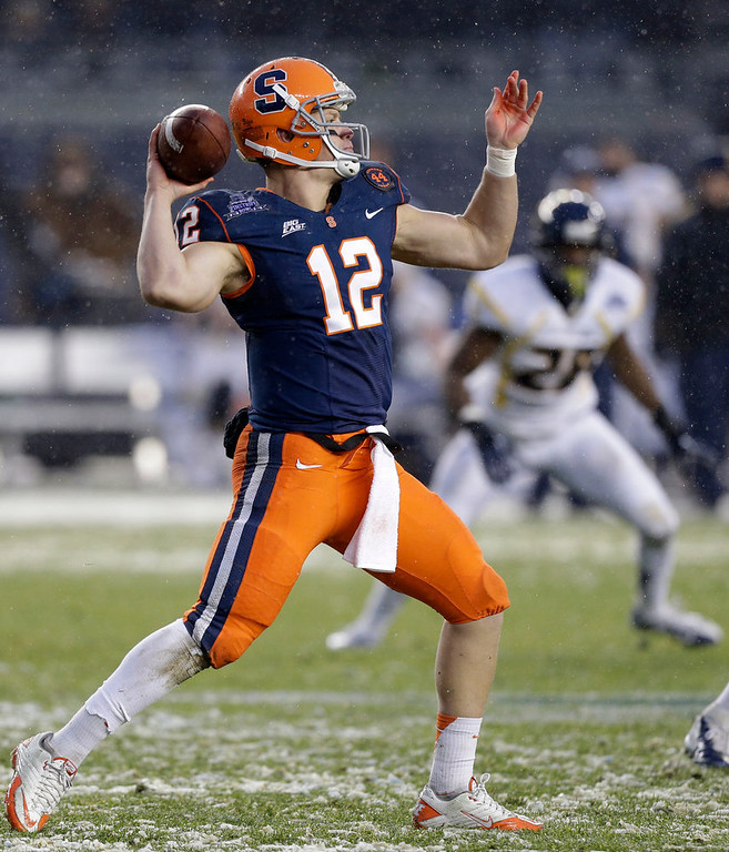 Description of . Syracuse quarterback Ryan Nassib (12) drops back for a pass against West Virginia during the Pinstripe Bowl NCAA college football game at Yankee Stadium in New York, Saturday, Dec. 29, 2012. (AP Photo/Kathy Willens)