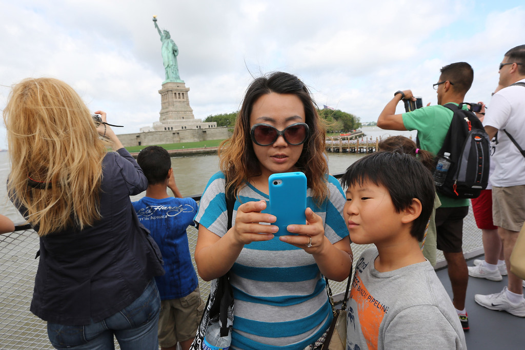 Description of . Visitors to fhe Statue of Liberty take photos as they arrive on the first tourist ferry to leave Manhattan, Thursday, July 4, 2013 at  in New York. The Statue of Liberty finally reopened on the Fourth of July months after Superstorm Sandy swamped its little island in New York Harbor as Americans across the country marked the holiday with fireworks and barbecues. (AP Photo/Mary Altaffer)