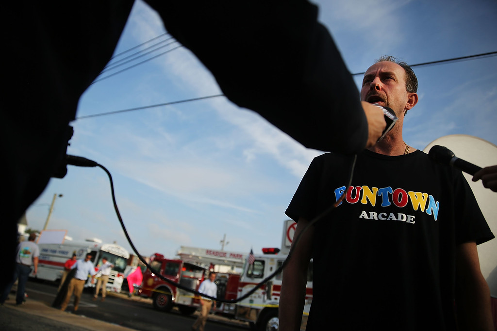 Description of . Daniel Shauger, manager at the heavily damaged Funtown Arcade, stands at the scene of a massive fire that destroyed dozens of businesses along an iconic Jersey shore boardwalk on September 13, 2013 in Seaside Heights, New Jersey.  (Photo by Spencer Platt/Getty Images)