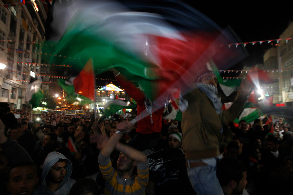 Description of . Palestinians wave palestinian flags as they watch the U.N. General Assembly votes on a resolution to upgrade the status of the Palestinian Authority to a nonmember observer state, In the west bank city of Ramallah, Thursday, Nov. 29, 2012.  The U.N. General Assembly has voted by a more than two-thirds majority to recognize the state of Palestine. The resolution upgrading the Palestinians' status to a nonmember observer state at the United Nations was approved by the 193-member world body late Thursday by a vote of 138-9 with 41 abstentions. (AP Photo/Majdi Mohammed)