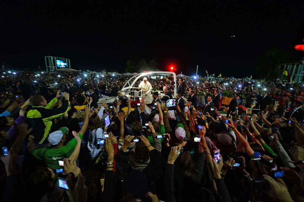 Description of . Pope Francis waves at faithfuls standing along the beachfront in Rio de Janeiro on his way for a prayer vigil with hundreds of thousands of young Catholic pilgrims attending World Youth Day (WYD) at Copacabana beach on July 27, 2013, during his week-long visit to Brazil.  CHRISTOPHE SIMON/AFP/Getty Images