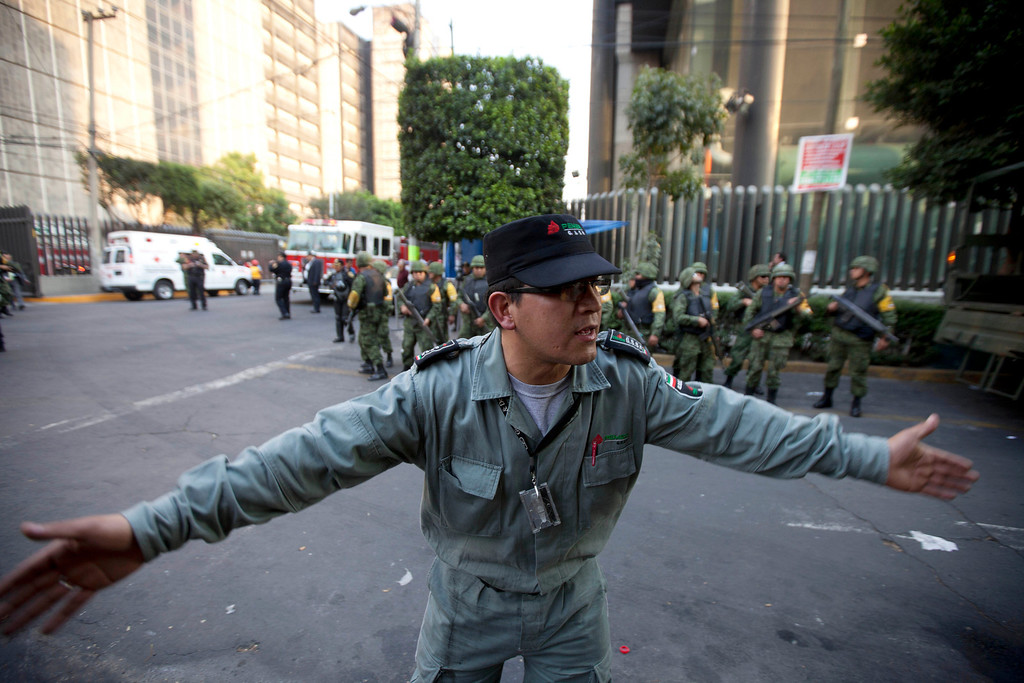 Description of . A worker belonging to Mexico's state-owned oil company PEMEX keeps journalists away after an explosion at an adjacent building to the executive tower of PEMEX in Mexico City, Thursday Jan. 31, 2013.   (AP Photo/Eduardo Verdugo)