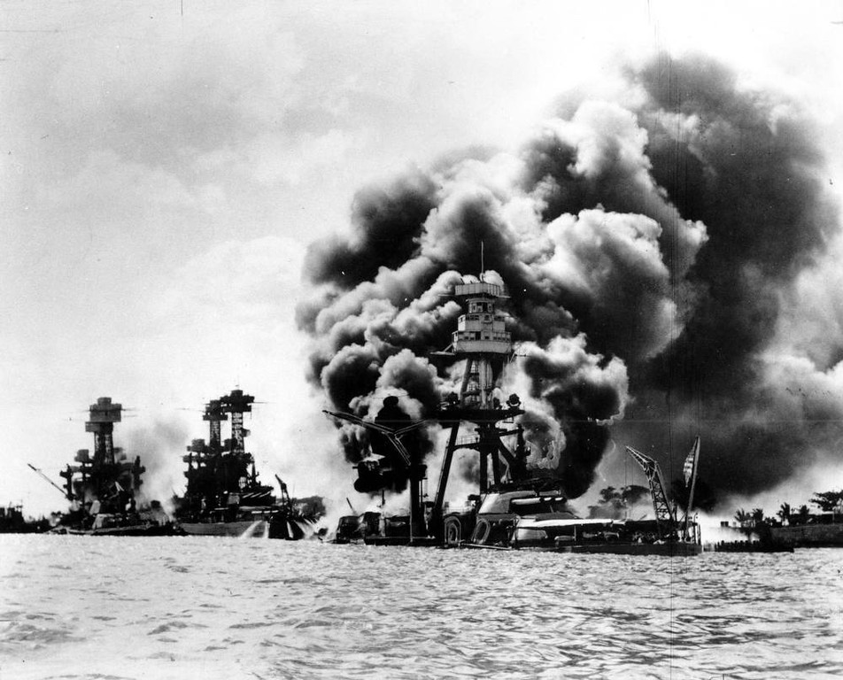Description of . Three U.S. battleships are hit from the air during the Japanese attack on Pearl Harbor on Dec. 7, 1941.  Japan's bombing of U.S. military bases at Pearl Harbor brings the U.S. into World War II. From left are: USS West Virginia, severely damaged; USS Tennessee, damaged; and USS Arizona, sunk.  (AP Photo)