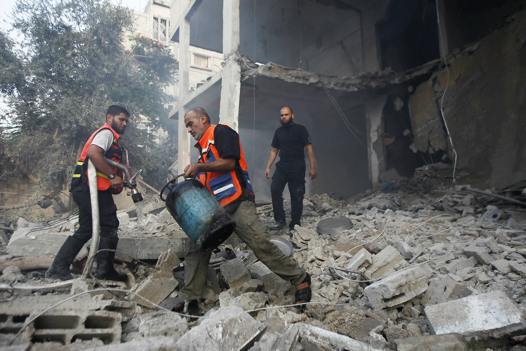 Description of . A Palestinian man carries a gas cylinder out of a building as others looks on  after the home was hit by an Israeli air strike in Rafah on July 29, 2014, in the southern of Gaza strip. Bloodshed in war-torn Gaza surged with dozens more Palestinians killed as the conflict raged into a fourth week and Iran accused Israel of genocide in the tiny enclave.  AFP PHOTO/ SAID  KHATIB/AFP/Getty Images