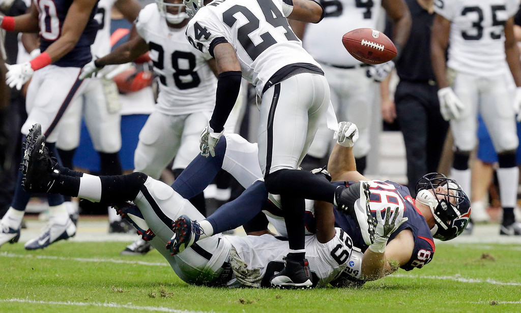 Description of . Houston Texans\' Garrett Graham (88) fumbles as he is hit by Oakland Raiders\' Lamarr Houston during the first half of an NFL football game Sunday, Nov. 17, 2013, in Houston. The Raiders recovered the fumble. (AP Photo/Patric Schneider)